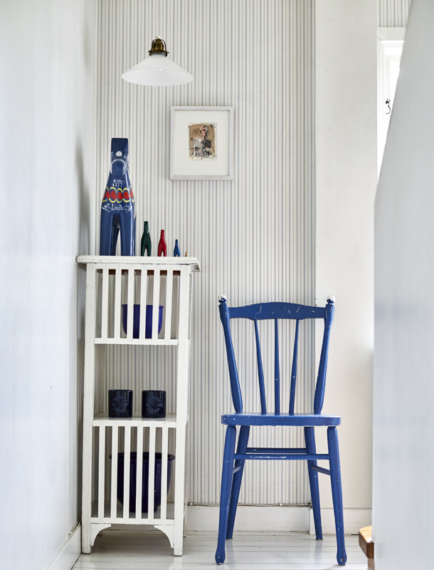 Kristina's stairway showcases three styling tips for a warm and pleasant space. Notice how she didn't cover every wall, how she uses her stairway to display her interior design chops, and lastly, how she uses the blue chair and ornaments to complement the striped wallpaper.
